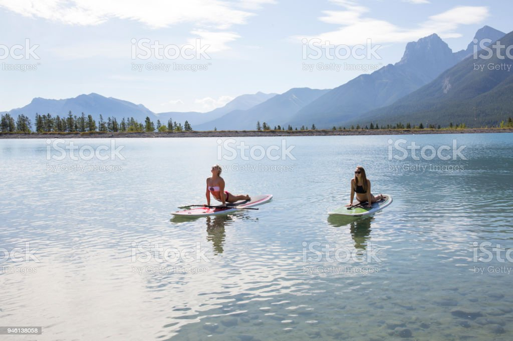 Two young women perform yoga moves on paddle boards on mountain lake stock photo