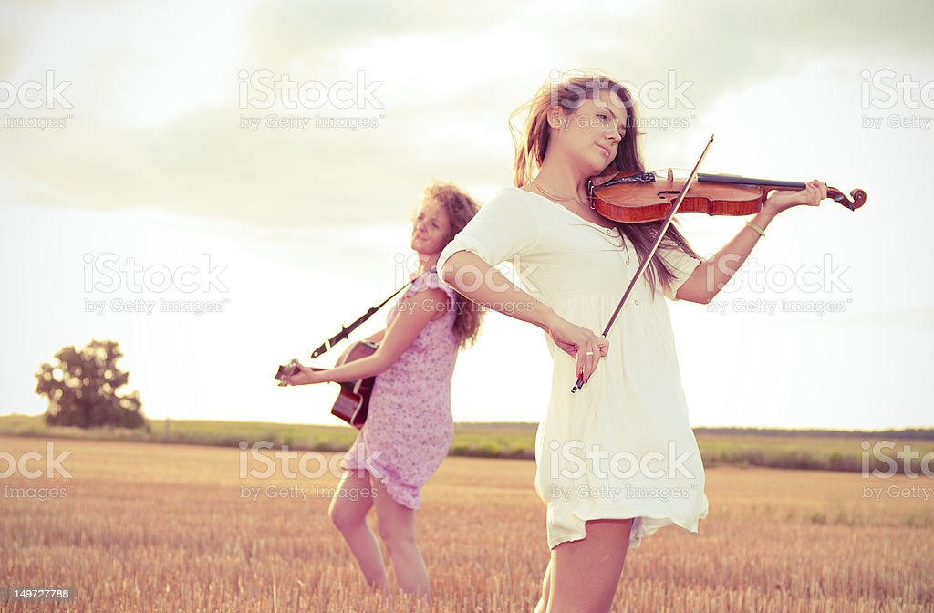 Two young women playing guitar and violin outdoors stock photo