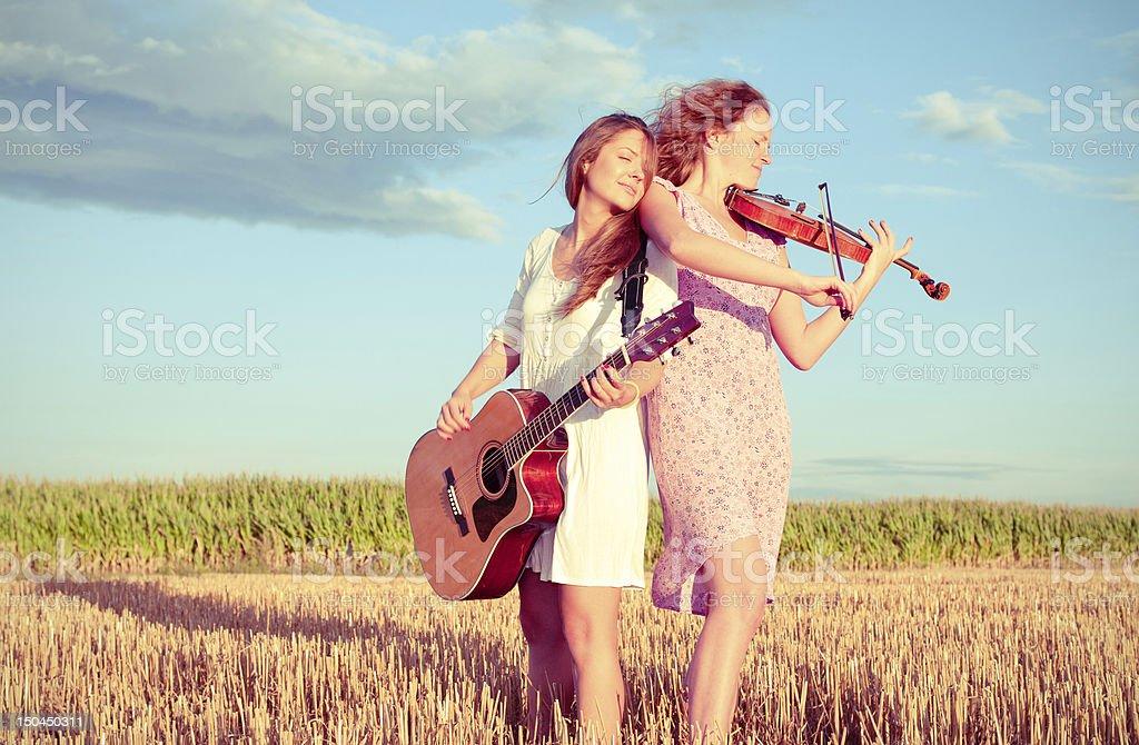 Zwei junge Frauen spielt Gitarre und Violine im Freien. Split toning – Foto