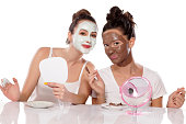 Two young women posing with face masks