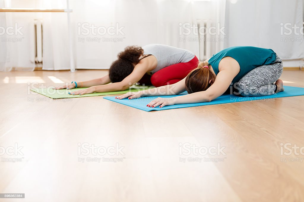 Two young women practicing yoga asana on floor in gym royalty-free stock photo