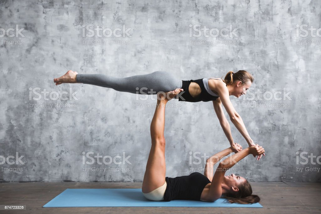 Two Young Women Practicing Yoga Poses And Asanas Stock Photo Download Image Now Istock