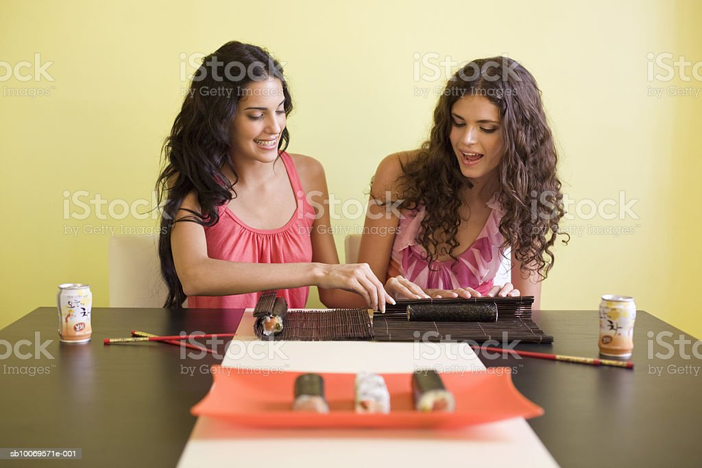 Two young women preparing sushi at home foto de stock royalty-free