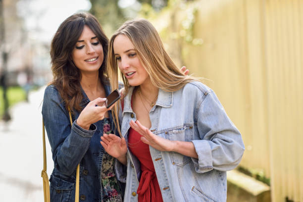 Two young women recording a voice message with smart phone stock photo