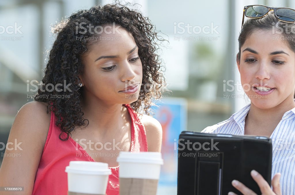 Two Young Women Reviewing Computer Tablet at a Cafe royalty-free stock photo