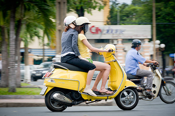 two young women riding a scooter in vietnam - motorbike, umbrella stock pictures, royalty-free photos & images