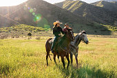 Two young adult women on horseback, riding through a meadow on a cattle ranch in rural Utah