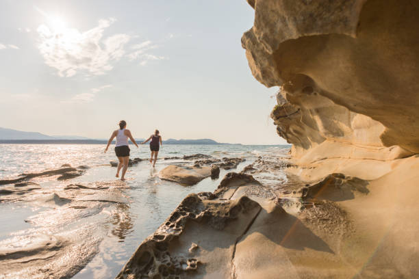 two young women running along ocean beach of sandstone formations - canada travel stock photos and pictures