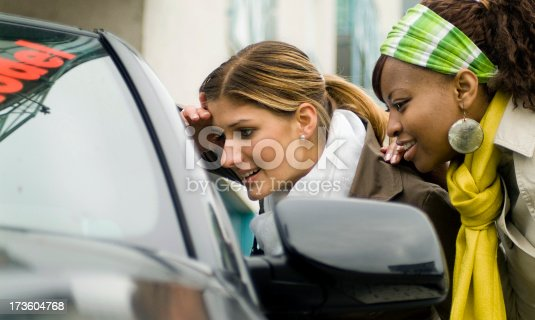 173607342 istock photo two young women shopping for a new car, looking in window 173604768