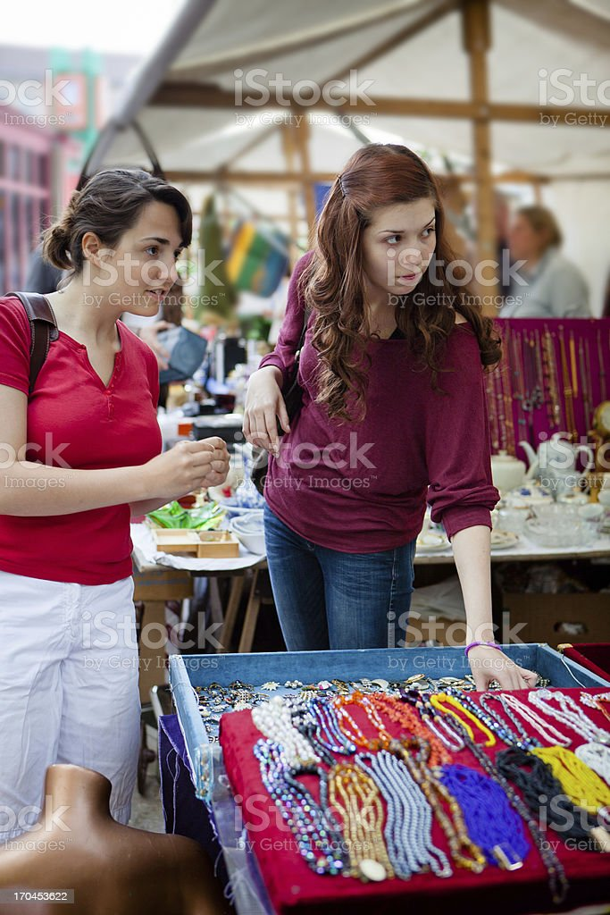 two young women shopping second hand at the flea market royalty-free stock photo