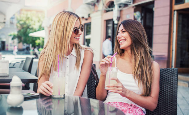 Two young women sitting in a cafe enjoying in lemonade and conversation. Consumerism, lifestyle concept stock photo