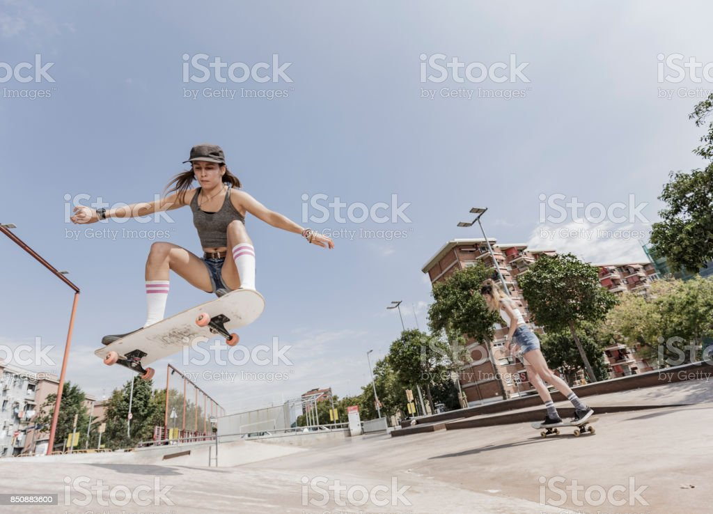 Two young women skateboarding and jumping stock photo