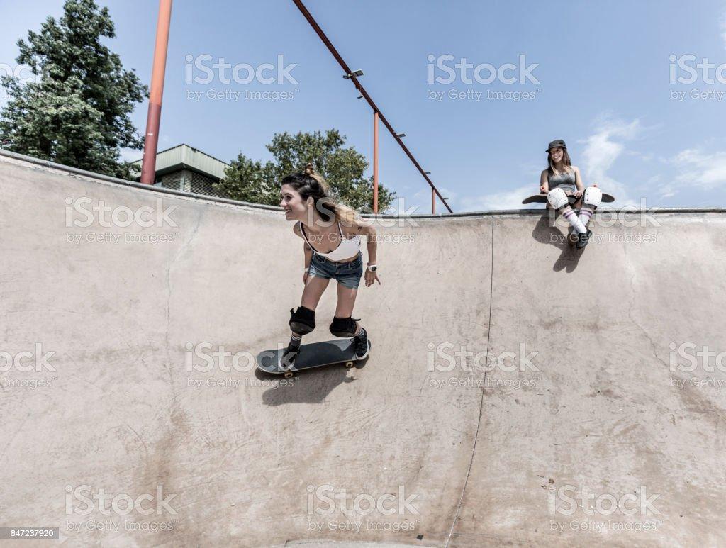 Two young women skateboarding stock photo