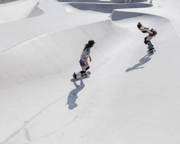 Twee jonge vrouwen, skateboarden foto