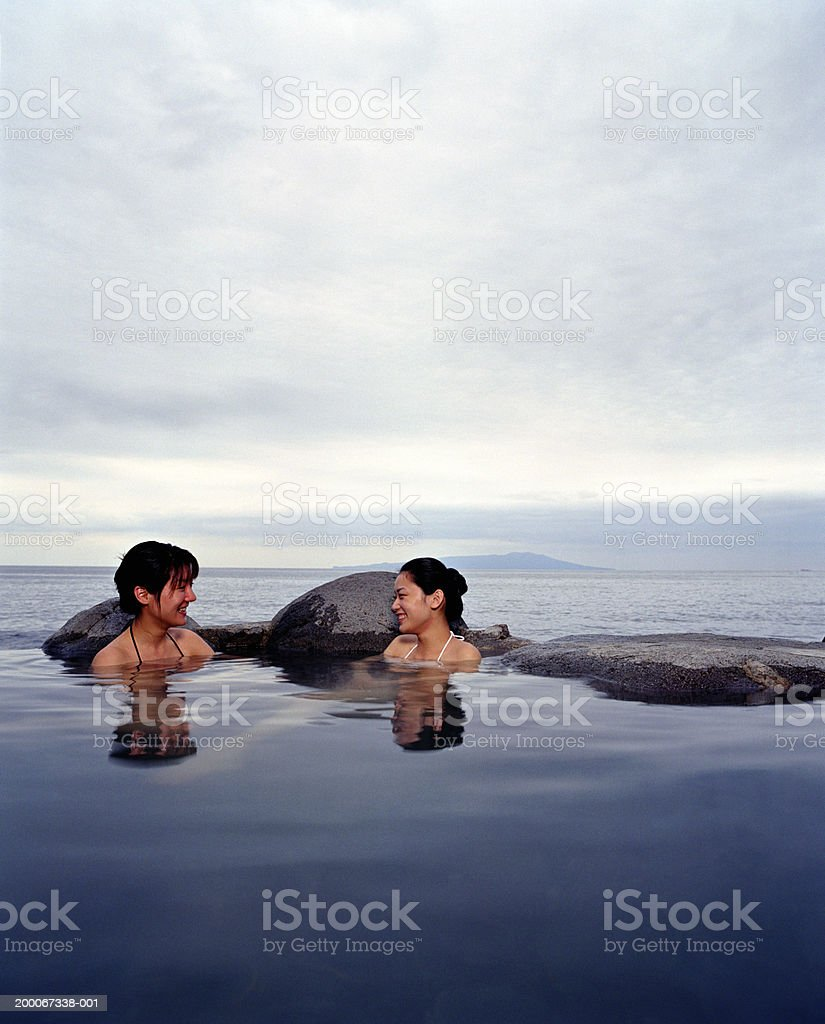 Two young women soaking in hot spring, sea in background royalty-free stock photo