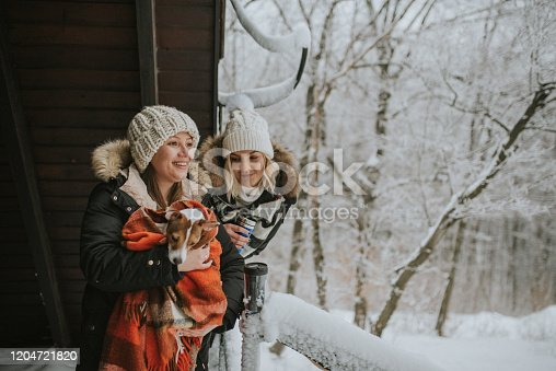 two young women ,friends or lesbian couple, spending winter holiday at village with their dog. standing on balcony.one of them is drinking tea.