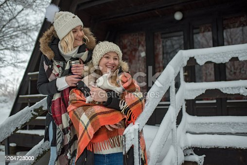 two young women ,friends or lesbian couple, spending winter holiday at village with their dog.One of them sitting on the stairs and other is drinking tea. winter time