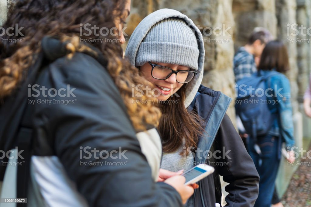 Two young women students taking a break in College entrance. stock photo