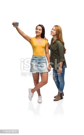 Two beautiful young women taking a selfie together wearing casual clothing isolated on a white background.