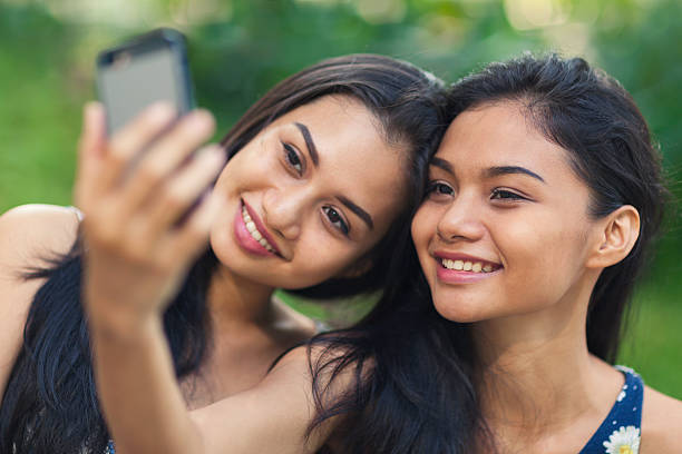 two young women taking a selfie - philippines girl stock photos and pictures