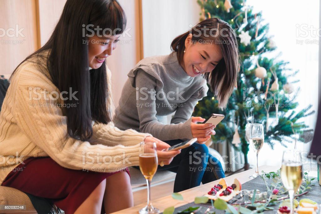 Two young women taking photos of their food at Christmas royalty-free stock photo
