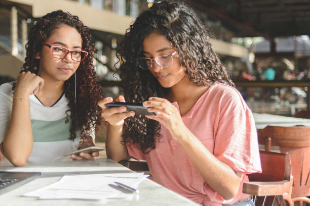 Two young women taking picture on smartphone of barcode for payment of bills via online banking app stock photo
