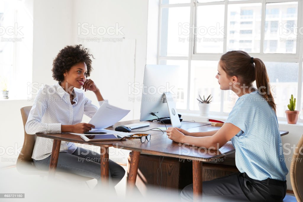 Two young women talking across their  desks in an office stock photo