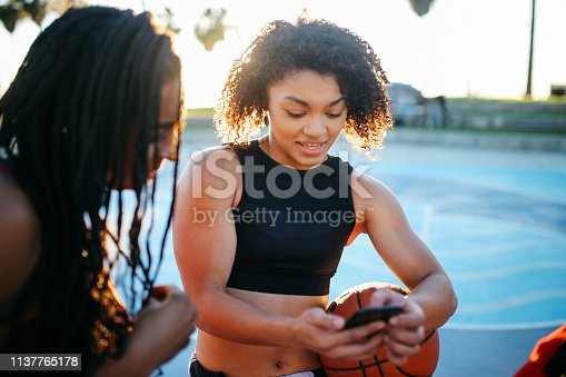 Portrait of two young women after playing basketball on the courts near Venice beach in Los Angeles, California. They are just chilling on a warm, summertime day after training.