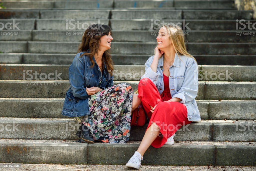 Two young women talking and laughing on urban steps stock photo