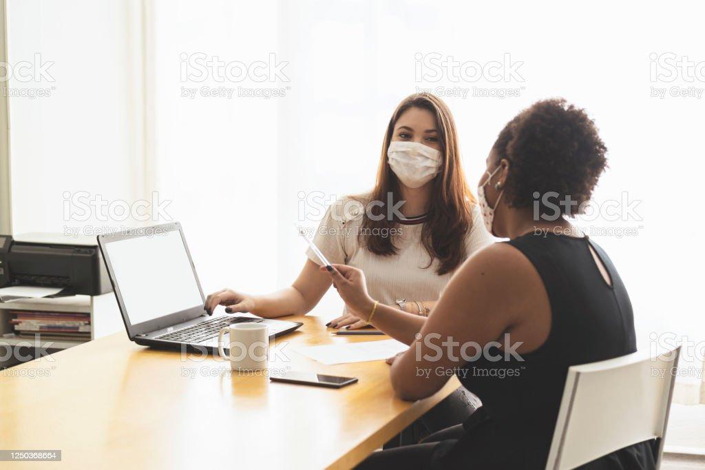 Twee jonge vrouwen die in een bureau spreken dat een beschermend gezichtsmasker draagt. - Royalty-free Afrikaanse etniciteit Stockfoto