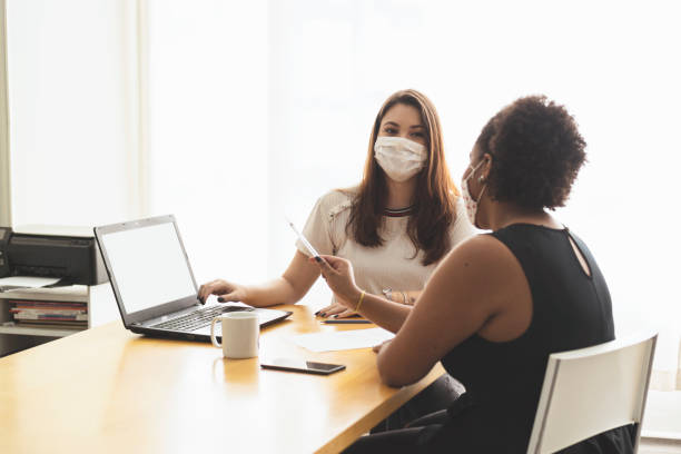 twee jonge vrouwen die in een bureau spreken dat een beschermend gezichtsmasker draagt. - medewerkerbetrokkenheid stockfoto's en -beelden