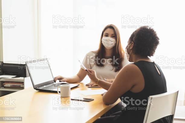 Twee Jonge Vrouwen Die In Een Bureau Spreken Dat Een Beschermend Gezichtsmasker Draagt Stockfoto en meer beelden van Afrikaanse etniciteit