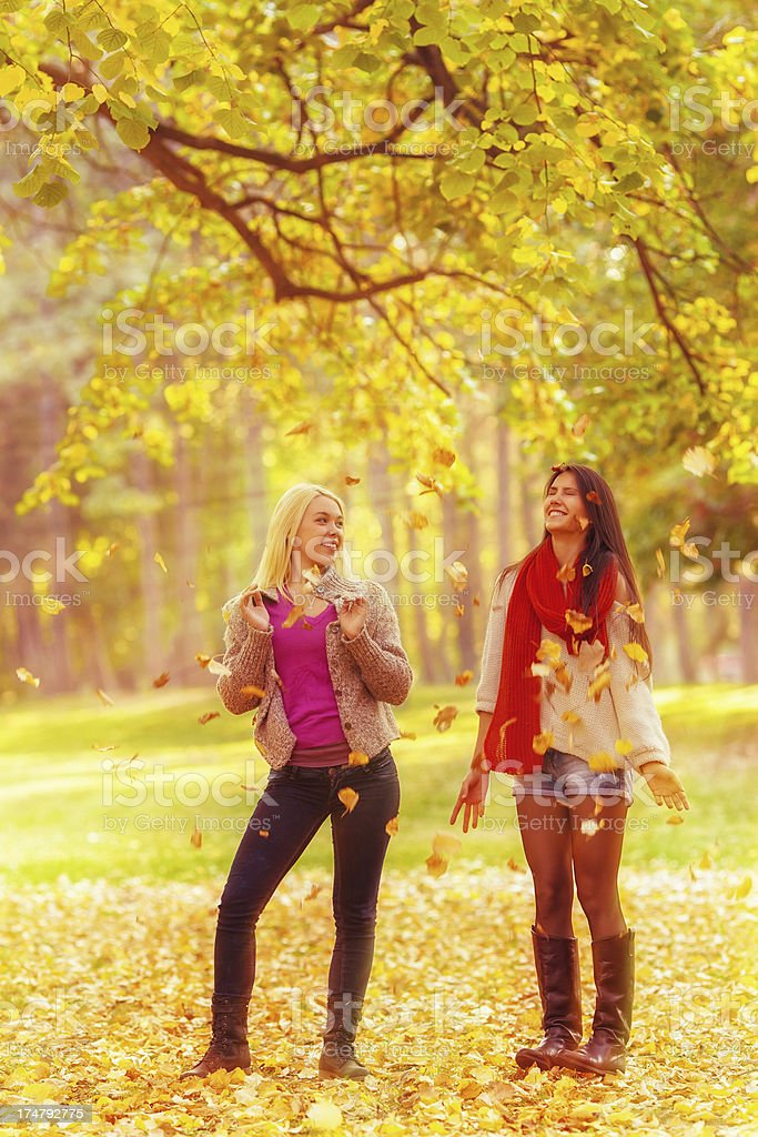 Two young women throwing autumn leaves in park royalty-free stock photo