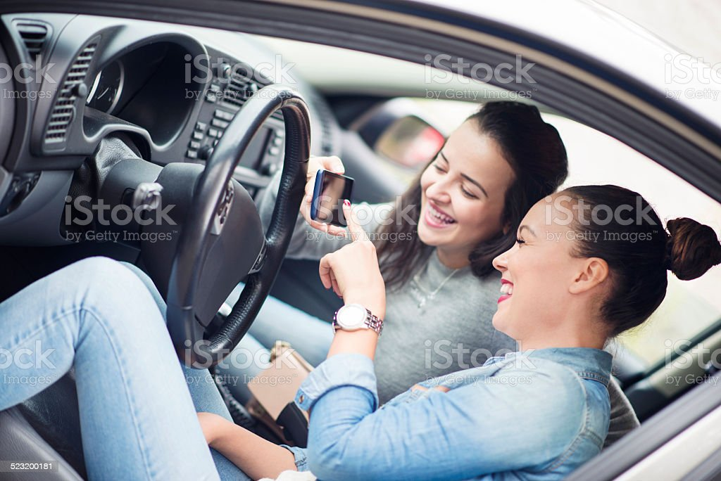 Two Young Women Touching GPS navigation in Car and Smiling stock photo