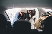 Two young women traveler traveling by car in winter.