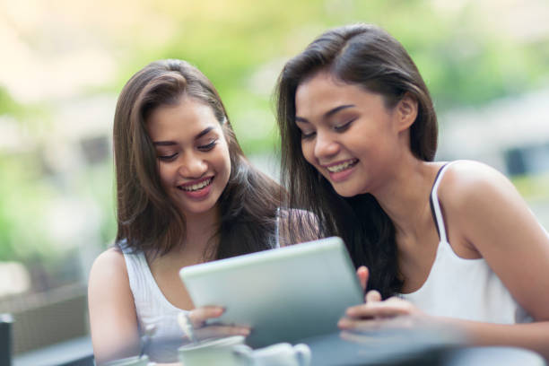 two young women using a tablet computer - philippines girl stock photos and pictures