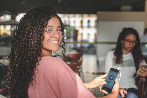 Two young women using financial app on smartphone stock photo