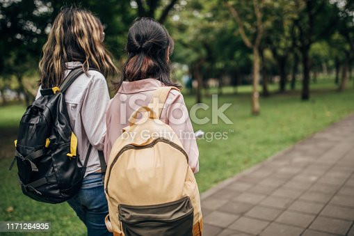 Two young female students walking in park