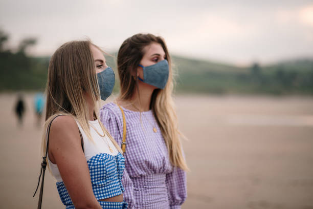 Two young women wearing protective face masks at the beach stock photo