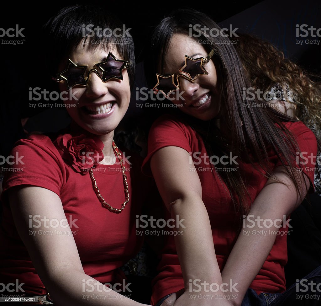 Two young women wearing star glasses at party, portrait royalty free stockfoto