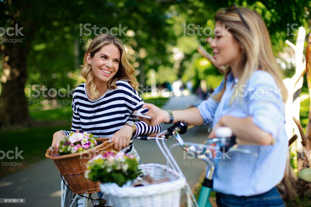 Zwei junge Frauen mit Fahrrädern mit Körben und Blumen – Foto