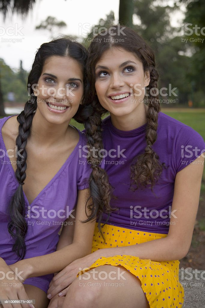 Two young women with plaits, sitting on park bench, portrait foto de stock libre de derechos