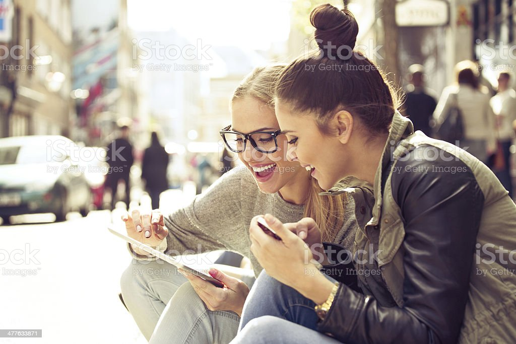 Two young women with tablet on street stock photo