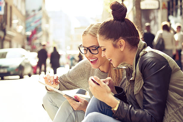 two young women with tablet on street - modern lifestyle stock photos and pictures