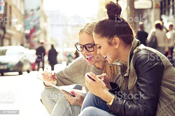 Two Young Women With Tablet On Street Stock Photo - Download Image Now