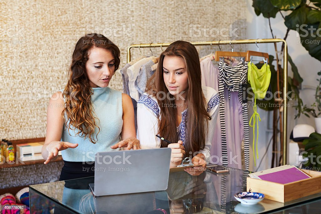 Two young women working in clothing store ストックフォト