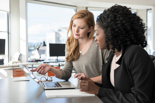 Two young women working in office with laptop stock photo