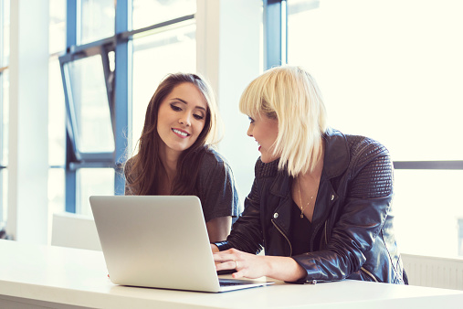 Two Young Women Working On Laptop Together Stock Photo - Download Image Now