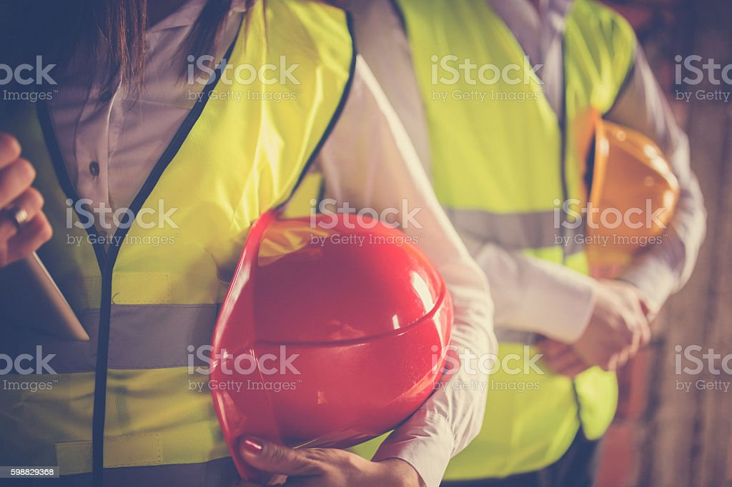 Two young workers hugging helmets stock photo