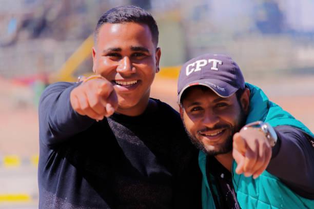 zwei junge arbeitnehmer stellen lachen - zum totlachen stock-fotos und bilder